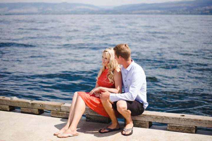 Engaged couple sitting on a dock