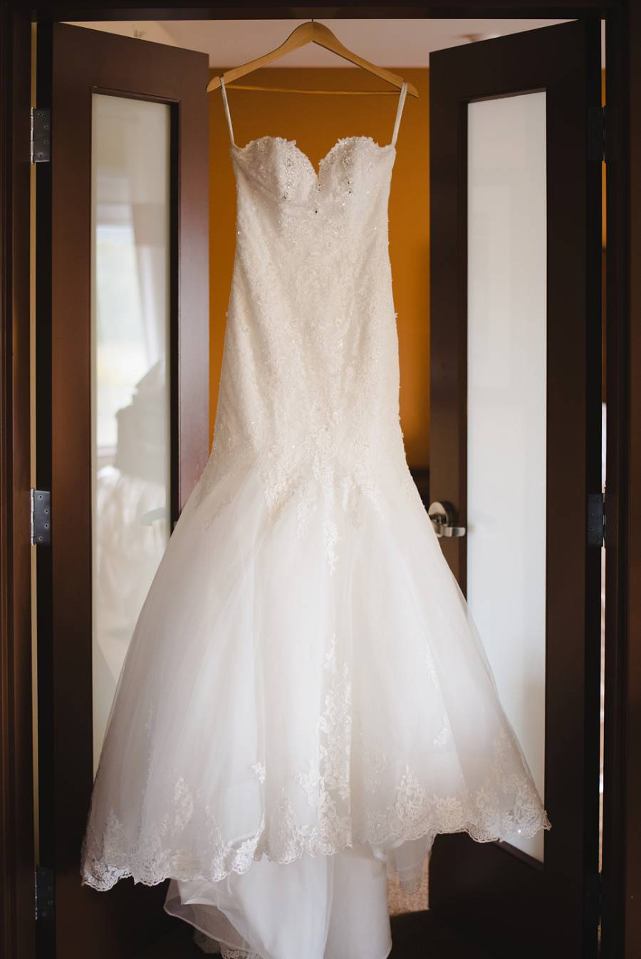 wedding dress hanging from a doorway