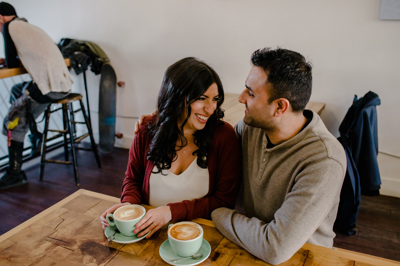 Man and woman laughing at a coffee shop in Kelowna during their engagement session