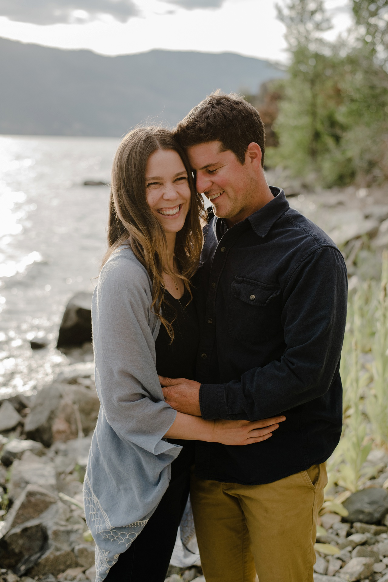 Couple smiling for engagement photos, holding each other