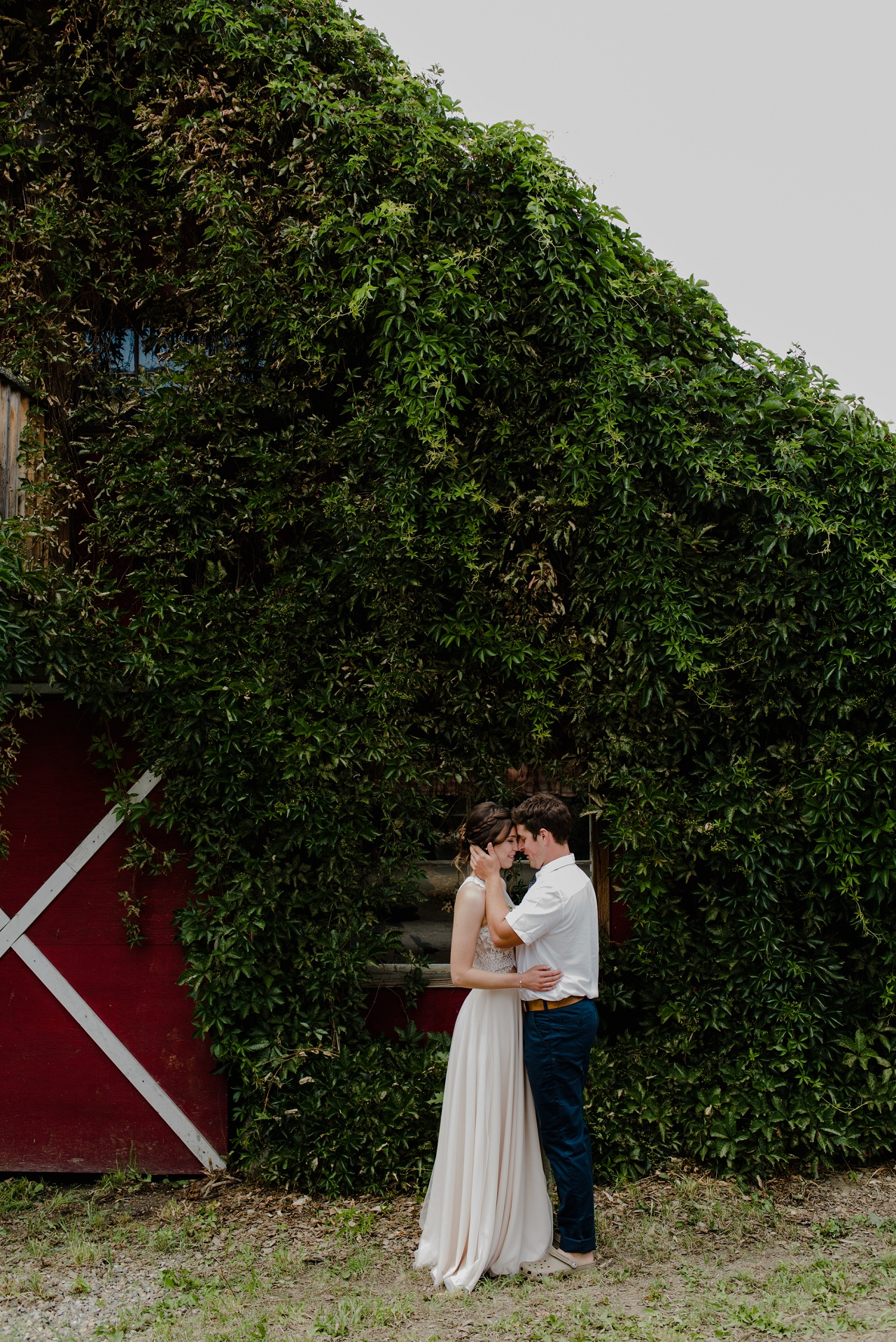 Bride and groom in front of a barn at Sproule's Farm, Lake Country