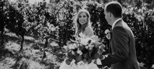 bride looking at her groom while walking through a vineyard
